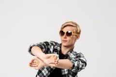 Lustige blonde hübsche tragende Sonnenbrille des jungen Mannes und zufälliges Tanzen des karierten Hemds, Kopienraum, über grauem Lizenzfreie Stockfotos