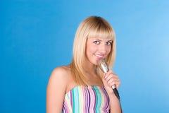 Lustige Blondine auf einem Blau mit einem Mikrofon Lizenzfreie Stockfotografie