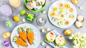 Lustige bunte Ostern-Nahrung für Kinder mit Dekorationen auf Tabelle Ostern-Abendessenkonzept lizenzfreie stockfotografie