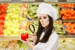 Lustige Dame Chef Inspecting Vegetables mit Lupe Lizenzfreie Stockfotografie