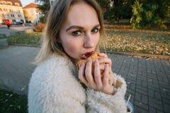 Lustige Frau der jungen Mode, die den Hamburger im Freien auf der Straße isst Lizenzfreies Stockfoto