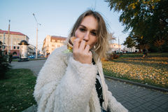 Lustige Frau der jungen Mode, die den Hamburger im Freien auf der Straße isst Stockfotografie
