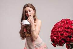 Lustige Frau, die Bonbons und Betrieb weg von Blumenstrauß isst stockfotos