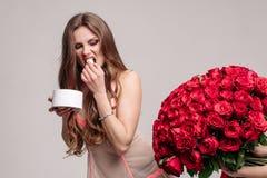 Lustige Frau, die Bonbons und Betrieb weg von Blumenstrauß isst stockfoto
