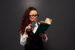 Lustige Frau, die das Buch mit Interesse liest Lizenzfreies Stockfoto