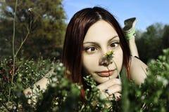Lustige Frau, die eine Blume riecht Stockfoto