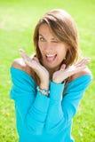 Lustige Frau, die im Gras blinzelt Lizenzfreie Stockfotos