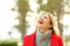 Lustige Frau, die oben im Winter schaut Stockfotografie