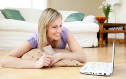 Lustige Frau, die online kauft, liegend auf dem Fußboden Stockbilder