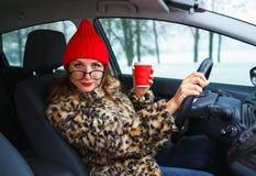 Lustige Frau in einem Pelzmantel und in einem roten Hut sprechend mit jemand während Stockfoto