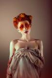 Porträt der ungewöhnlichen Redhead-Frau mit den falschen roten Wimpern. Fantasie Stockfotos