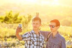 Lustige Freundkerle werden auf Telefon selfie an einem sonnigen Tag fotografiert lizenzfreies stockbild