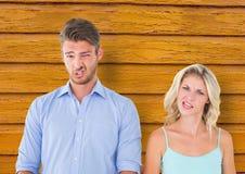 lustige Gesichter der Paare mit gelbem hölzernem Hintergrund Stockfoto