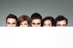 Lustige Gesichter hinter weißem Vorstand Lizenzfreie Stockbilder
