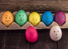 Lustige Gesichter Ostereier auf hölzernem Hintergrund Lustige Dekoration Stockfotografie
