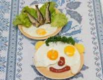 Lustige Gesichter von den Eiern mit Käse und Soße Lizenzfreie Stockfotos