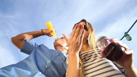 Lustige getrunkene Paare, die unten Kamera, trinkenden Cocktails und dem Lachen betrachten stock footage