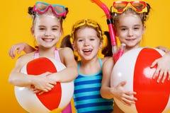 Lustige lustige glückliche Kinder in Badeanzügen und in schwimmenden Gläsern Stockbilder
