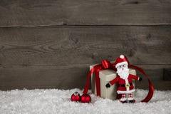 Lustige handgemachte Sankt mit einem roten Weihnachtsgeschenk auf hölzerner Rückseite Lizenzfreie Stockfotografie
