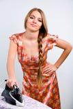 Lustige Hausfrau mit elektrischem Eisen Lizenzfreie Stockfotos