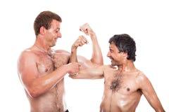 Lustige hemdlose Männer vergleichen Muskeln Stockbilder