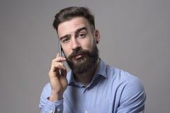 Lustige hochgezogene Augenbraue verwirrte Gesichtsausdruck des jungen Geschäftsmannes, der am Telefon spricht, das Kamera betrach stockfotografie