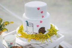 Lustige Hochzeitstorte vom Mastix mit einer Schale Milch Lizenzfreies Stockfoto