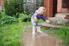 Lustige 2 Jahre alte Baby, die in der Pfütze spielen. Stockfoto