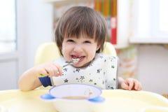 Lustige 2 Jahre Junge, die Suppe essen Stockbild
