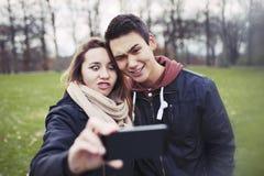 Lustige Jugendpaare, die sich fotografieren Stockbilder