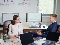 Lustige junge Büroangestellte stehen an dem Arbeitsplatz in Verbindung Stockfoto