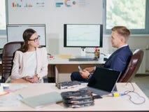 Lustige junge Büroangestellte stehen an dem Arbeitsplatz in Verbindung Lizenzfreie Stockbilder