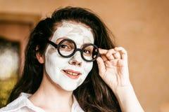 Lustige junge Frau, die eine tiefe Reinigungslehmmaske anwendet Stockfotos