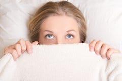 Lustige junge Frau, die im Bett unter Decke und dem Träumen liegt Stockbilder