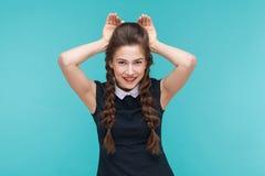 Lustige junge Frau, die Kaninchenzeichen und -lächeln zeigt lizenzfreie stockfotos