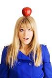 Lustige junge Frau mit einem Apfel auf ihrem Kopf Stockfotografie