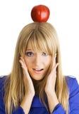 Lustige junge Frau mit einem Apfel auf ihrem Kopf Lizenzfreies Stockfoto
