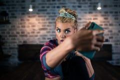 Lustige junge Frau zeigt Zunge und von Smartphone in camera schauen Lizenzfreie Stockbilder