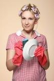 Lustige junge Hausfrau mit den Handschuhen, die scrubberr anhalten Stockfoto