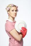Lustige junge Hausfrau mit Handschuhen auf weißem Hintergrund. Lizenzfreie Stockfotografie