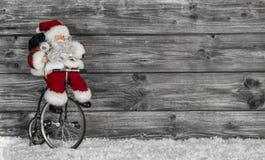 Lustige kaufende Weihnachtsgeschenke Sankt verziert auf hölzernem backgr Stockfotos