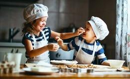 Lustige Kinder der glücklichen Familie backen Plätzchen in der Küche stockfotos