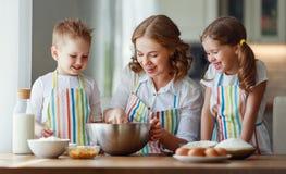 Lustige Kinder der gl?cklichen Familie backen Pl?tzchen in der K?che stockbild
