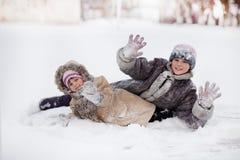 Lustige Kinder, die auf Park des verschneiten Winters spielen und lachen stockbild