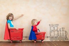 Lustige Kinder, die das Spielzeugauto Innen fahren lizenzfreie stockfotografie