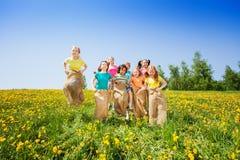 Lustige Kinder, die in die Säcke zusammen spielen springen Lizenzfreies Stockbild