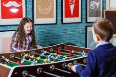 Lustige Kinder, die Tischfußball in einem Café am Valentinstag spielen Stockbild