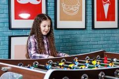 Lustige Kinder, die Tischfußball in einem Café am Valentinstag spielen Lizenzfreie Stockfotos