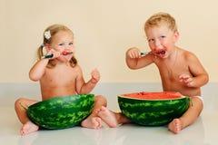 Lustige Kinder, die Wassermelone essen Stockfotos