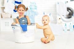 Lustige Kinder glückliche Schwester und Bruder der kleinen Helfer in der Wäscherei zu Stockfotos